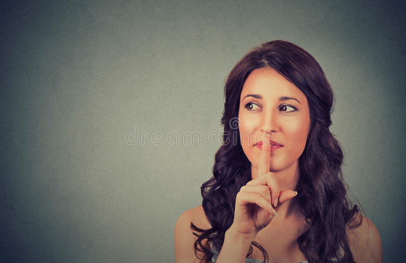 Stående av den attraktiva tonårs- flickan med fingret på kanter, begrepp av studentshowtystnaden, tystnad, hemlig gest, ung nätt  royaltyfri foto