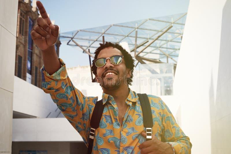 Stående av den attraktiva unga afrikansk amerikanhipsteren i tillfälliga kläder och solglasögon som ler och pekar handen _ royaltyfria bilder