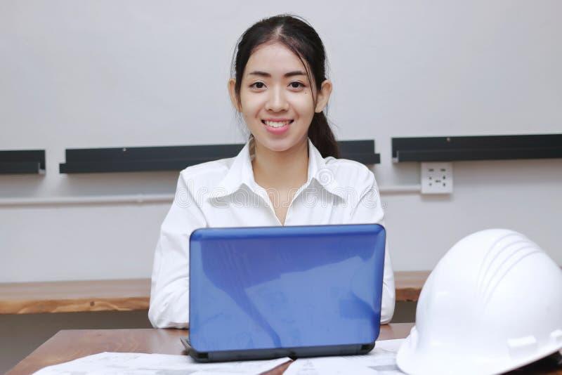 Stående av den attraktiva unga asiatiska affärskvinnan som i regeringsställning arbetar på arbetsplatsen Tänka och fundersam affä royaltyfria foton