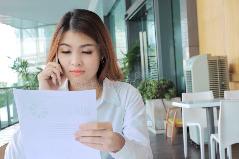 Stående av den attraktiva unga asiatiska affärskvinnan som i regeringsställning talar på telefonen mot hållande dokumentmappar på arkivbilder