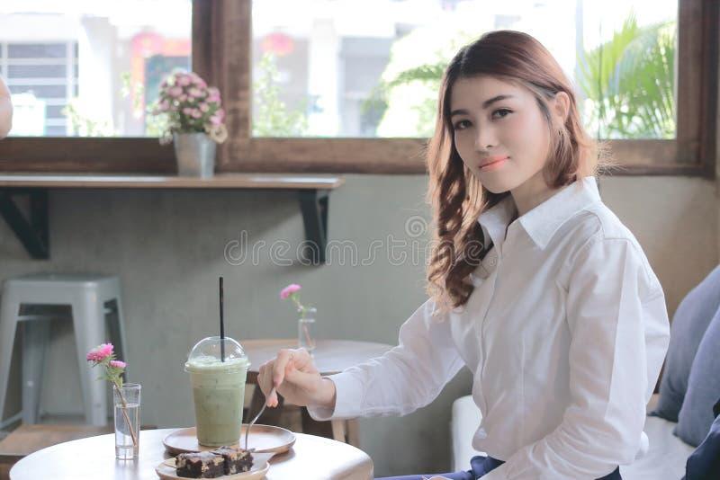Stående av den attraktiva unga asiatiska kvinnan som äter nisseefterrätten med gaffeln i kaffekafé royaltyfri foto