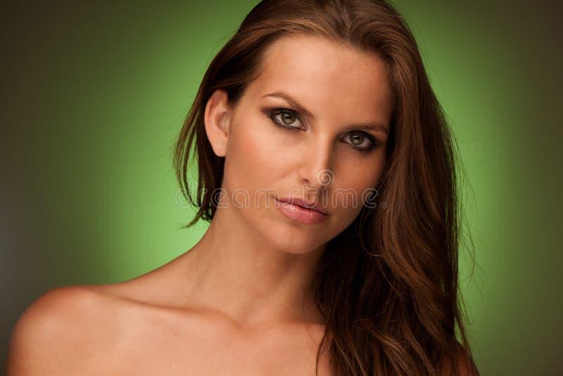 Stående av den attraktiva unga brunettkvinnan på grön studiobaksida royaltyfria foton
