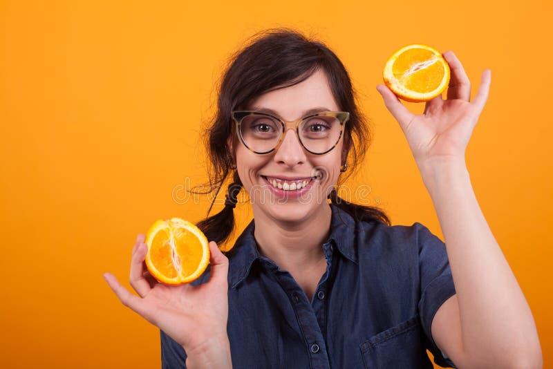 Stående av den attraktiva unga kvinnan med exponeringsglas som ler och visar nya apelsiner på kameran i studio över guling royaltyfria foton