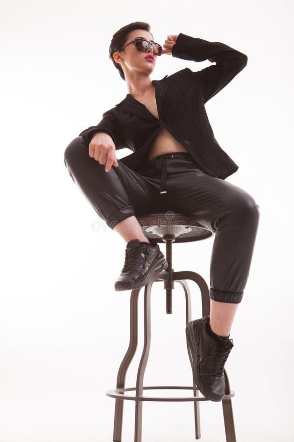 Stående av den attraktiva unga kvinnan som sitter på en stol som poserar i studio över vit bakgrund royaltyfri foto