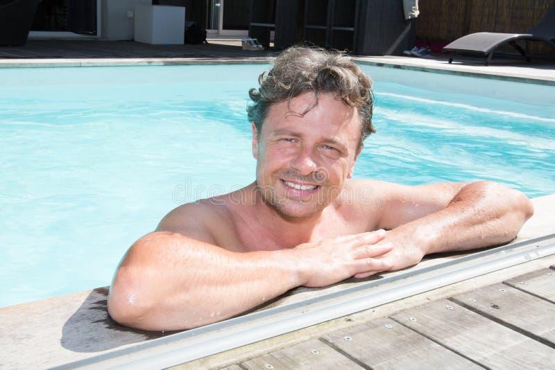 Stående av den attraktiva unga mannen på kanten av den hem- simbassängen fotografering för bildbyråer