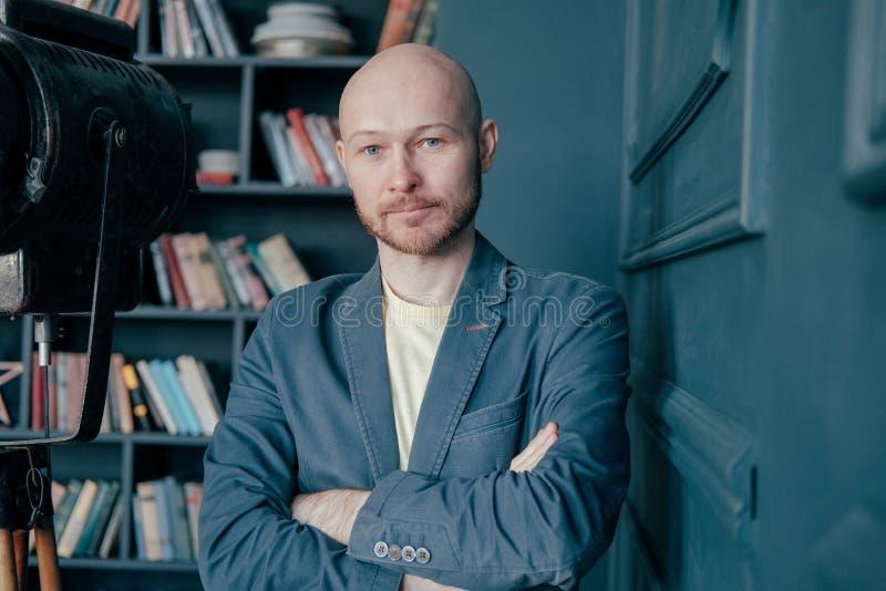 Stående av den attraktiva vuxna lyckade skalliga mannen med skägget i dräkt mot bokväggen royaltyfri bild