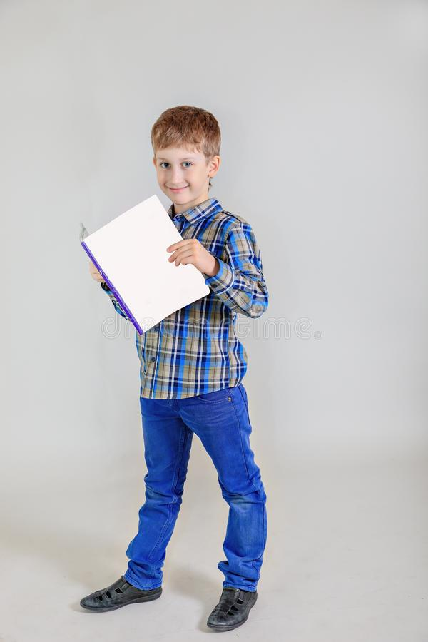 Stående av den aucasian pojken för gullig  för rödhårig man Ñ, grundskolastudent med boken på grå bakgrund royaltyfri fotografi