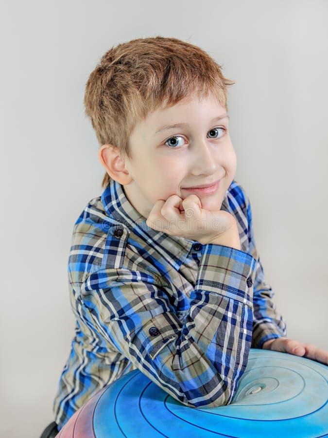 Stående av den aucasian pojken för gullig  för rödhårig man Ñ, grundskolastudent på grå bakgrund arkivfoton