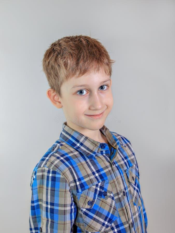 Stående av den aucasian pojken för gullig  för rödhårig man Ñ, grundskolastudent på grå bakgrund royaltyfri foto