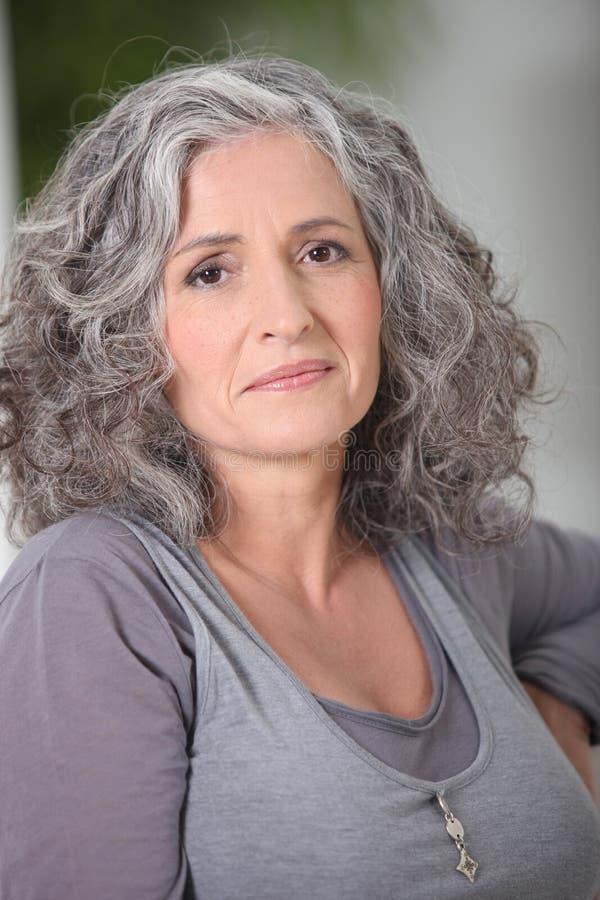 Avkopplad grå färg-haired kvinna royaltyfri bild