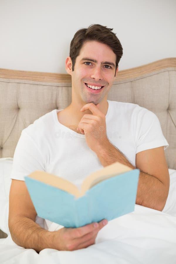 Stående av den avkopplade läseboken för ung man i säng arkivbilder