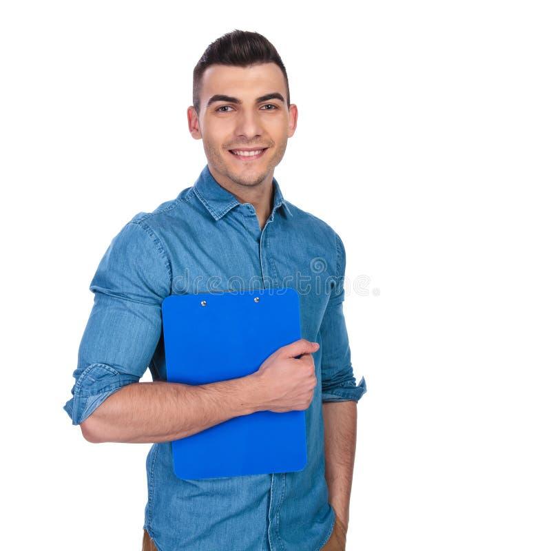 Stående av den avkopplade tillfälliga mannen som rymmer den blåa skrivplattan fotografering för bildbyråer
