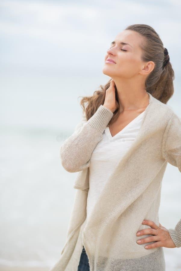 Stående av den avkopplade unga kvinnan på den kalla stranden royaltyfri fotografi