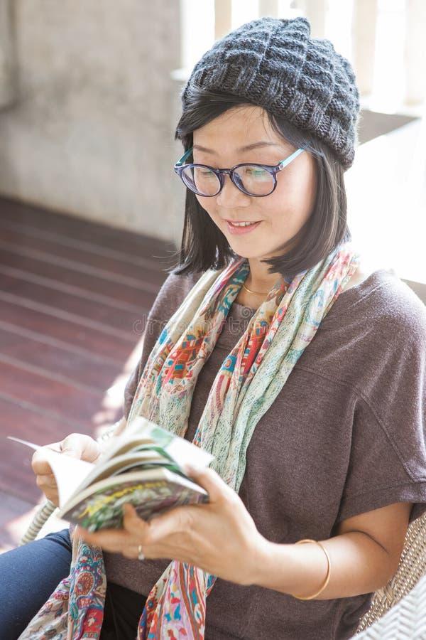 Stående av den avslappnande tidläseboken för härlig asiatisk kvinna på arkivfoto