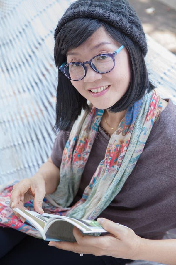 Stående av den avslappnande tidläseboken för härlig asiatisk kvinna på arkivbild