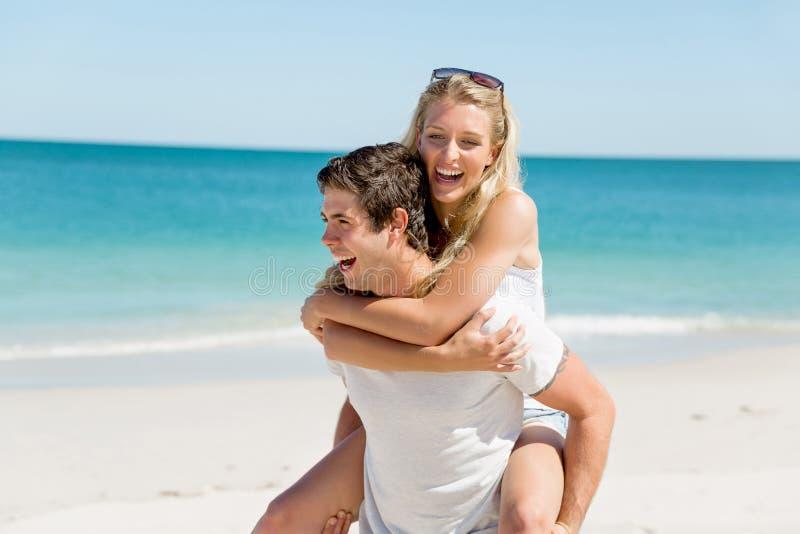 Stående av den bärande flickvännen för man på hans baksida arkivfoton