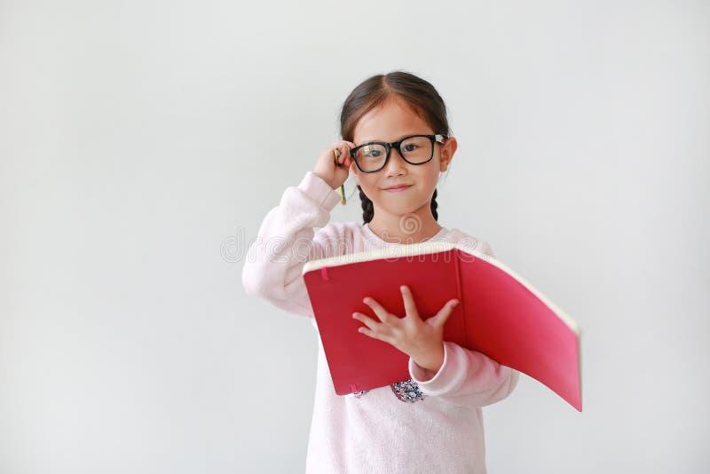Stående av den bärande glasögon för liten asiatisk skolflicka och rymmaanteckningsboken med blyertspennan på vit bakgrund fotografering för bildbyråer