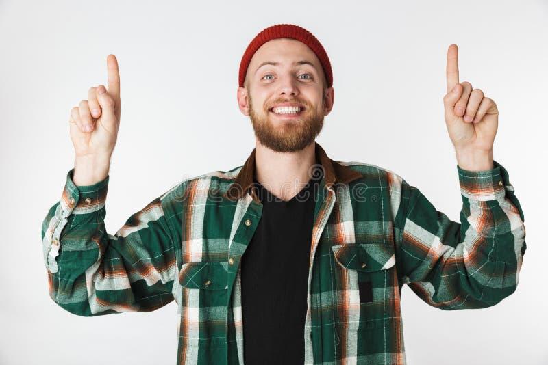 Stående av den bärande hatten för stilig man och plädskjortan som ler, medan peka fingrar som isoleras uppåt över vit bakgrund royaltyfria foton