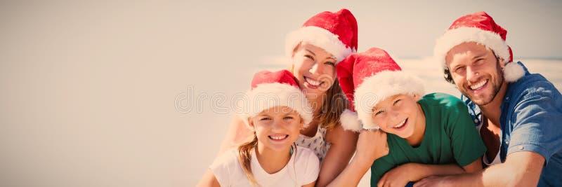 Stående av den bärande jultomtenhatten för lycklig familj på stranden arkivfoton