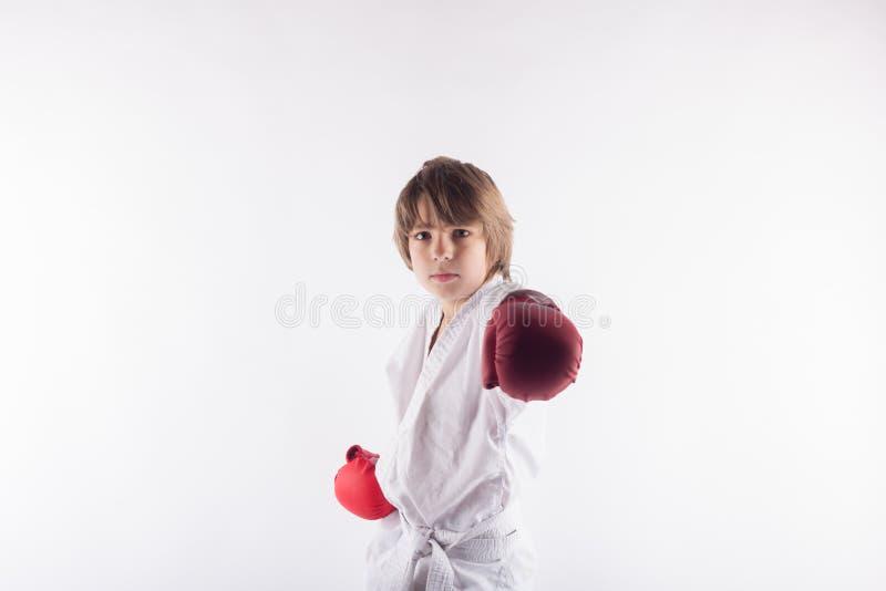 Stående av den bärande kimonot för karateunge och röda boxninghandskar fotografering för bildbyråer