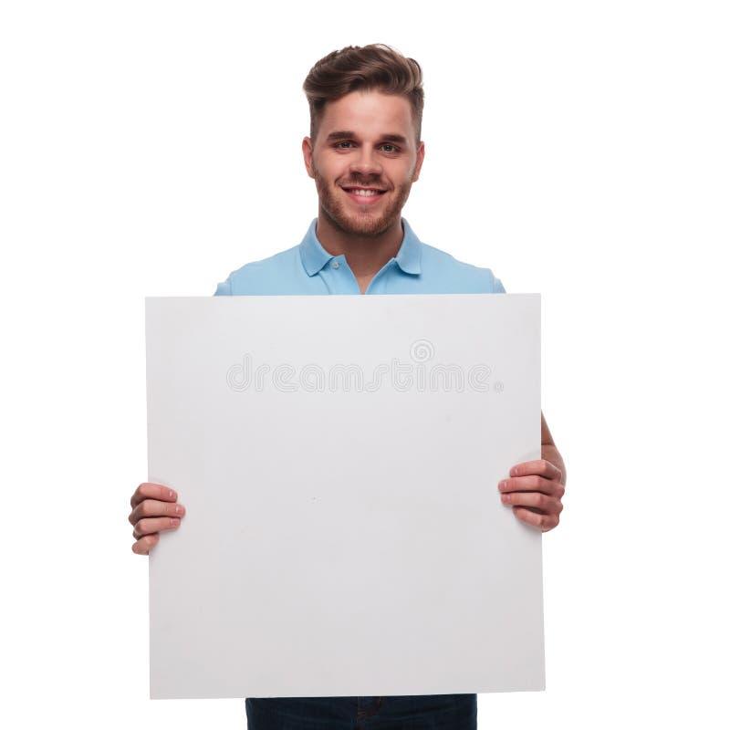 Stående av den bärande poloskjortan för ung man som rymmer det tomma tecknet fotografering för bildbyråer