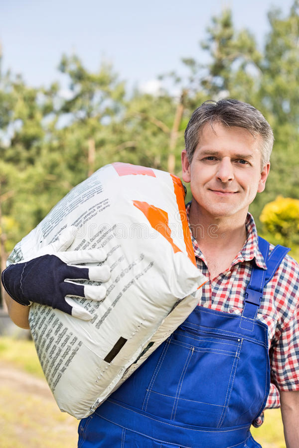 Stående av den bärande säcken för säker trädgårdsmästare i växtbarnkammare royaltyfri foto