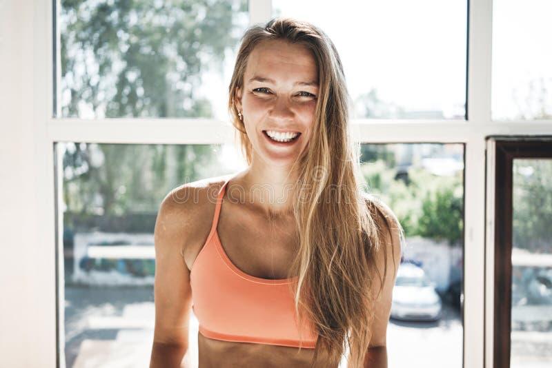 Stående av den bärande sportwearen för solbrännapassformkvinna i solig vit idrottshall royaltyfri fotografi