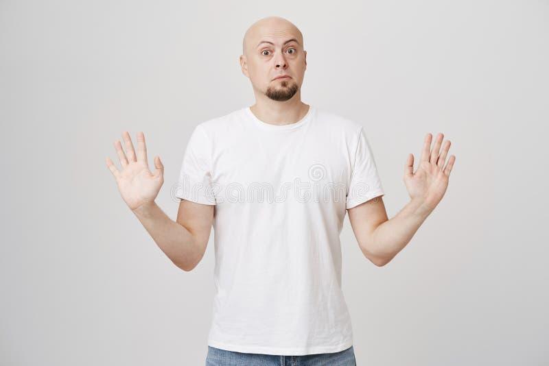 Stående av den bedövade angelägna skalliga caucasian skäggiga mannen som lyfter händer i kapitulationgest som ser med poppade ögo royaltyfri bild