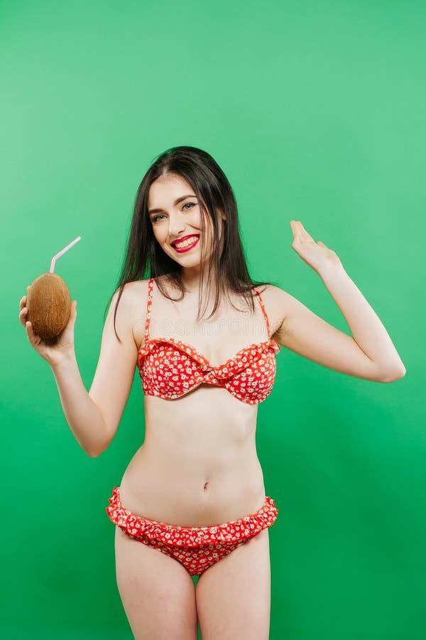 Stående av den bekymmerslösa flickan i den ljusa baddräkten som poserar med coctailen i studio på grön bakgrund fotografering för bildbyråer