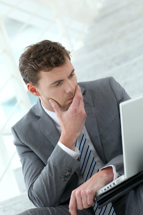 Stående av den bekymrade affärsmannen som arbetar på bärbara datorn arkivbild