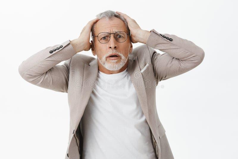 Stående av den bekymrade och besvärade chockade höga mannen med vitt hår och skägg i dräkt och exponeringsglas som rymmer på händ arkivbild