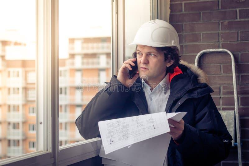 Stående av den bekymrade orakade byggmästaren som berättar vid mobilen, medan hålla olika projekt i hand Kommunikation och royaltyfri bild