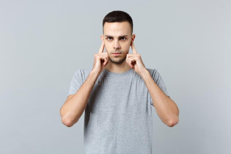 Stående av den bekymrade unga mannen i tillfällig kläder som ser kameran som täcker öron med fingrar som isoleras på den gråa väg royaltyfria foton