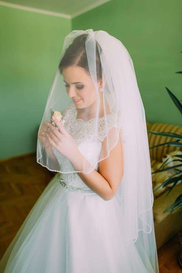 Stående av den beslöjade sinnliga unga bruden med blomman royaltyfria foton