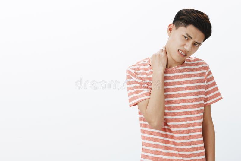 Stående av den besvärade oroliga unga asiatiska mannen i den randiga t-skjortan som är ovillig att göra något gnuggbildhals som v arkivfoton