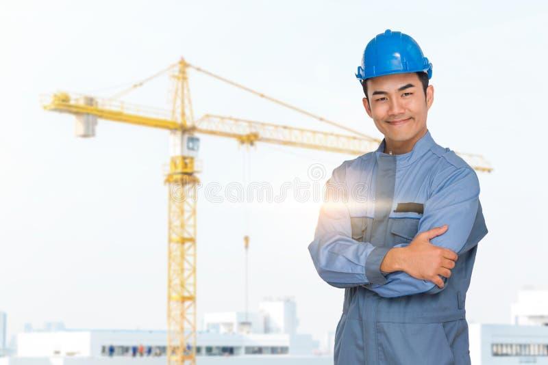 Stående av den blåa hjälmen för teknikerkläder som är saefty på konstruktionsplats med kranbakgrund arkivfoto