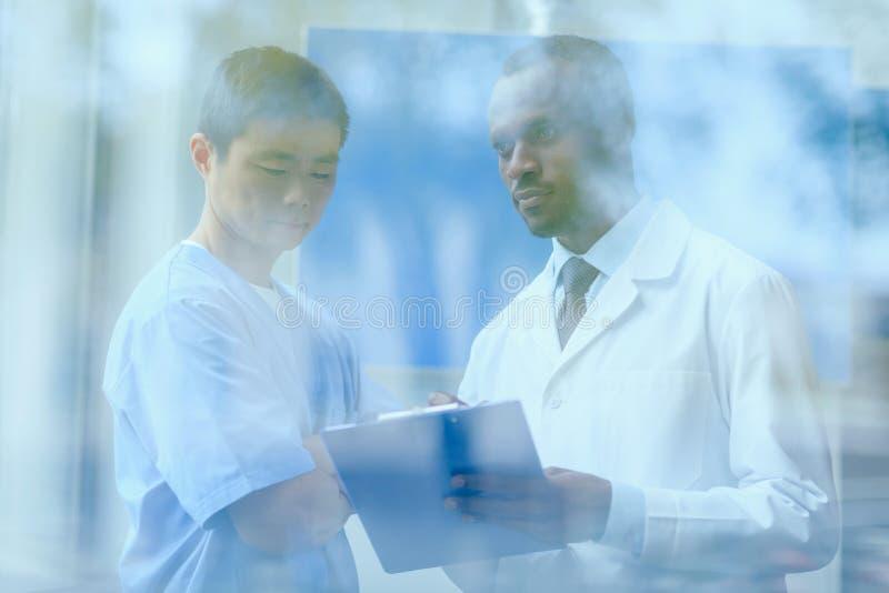 stående av den blandras- gruppen av doktorer i medicinska likformig arkivbilder