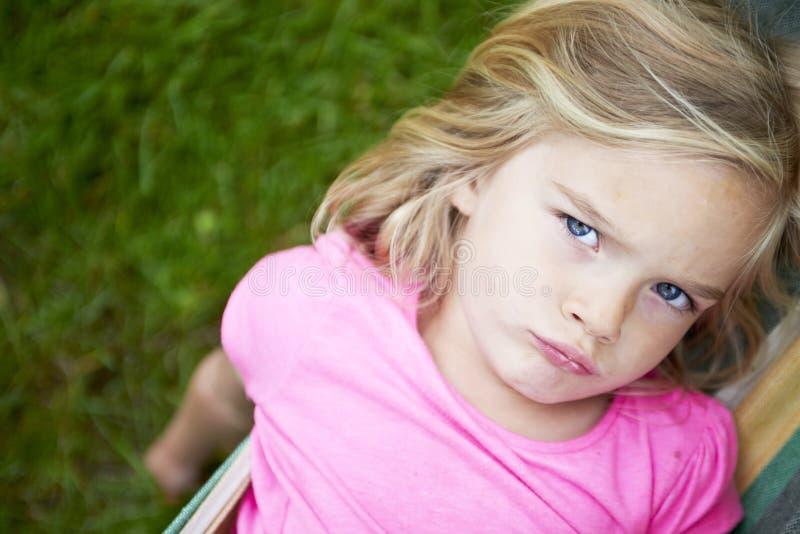 Stående av den blonda barnflickan med blåa ögon som ser kameran som kopplar av på en färgrik hängmatta royaltyfria foton