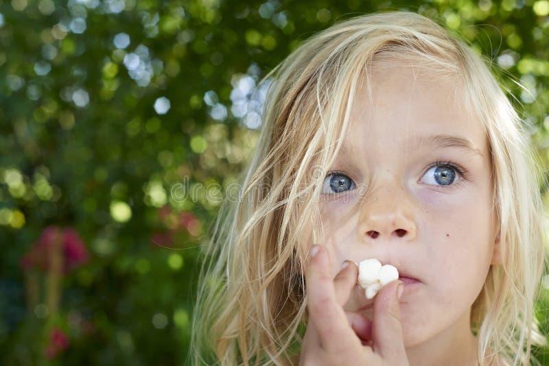Stående av den blonda flickan för barn som äter popcorn royaltyfri bild
