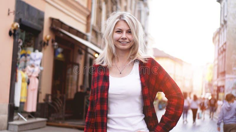 Stående av den blonda flickan med ovårdat hår som bär den röda skjortan, vit t-skjorta royaltyfria foton