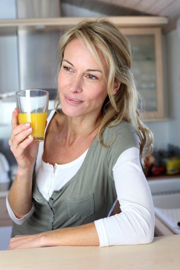 Stående av den blonda kvinnan som dricker orange fruktsaft royaltyfri bild