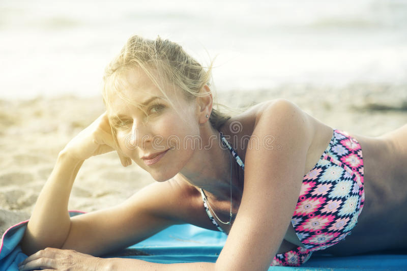 Stående av den blonda kvinnan som ligger på stranden arkivbild