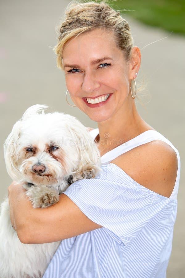 Stående av den blonda kvinnan som rymmer en gullig liten vit hund arkivfoton