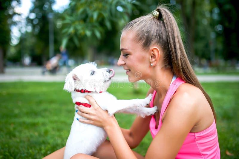 Stående av den blonda kvinnlign som lite spelar med den vita hunden, bichon royaltyfria bilder