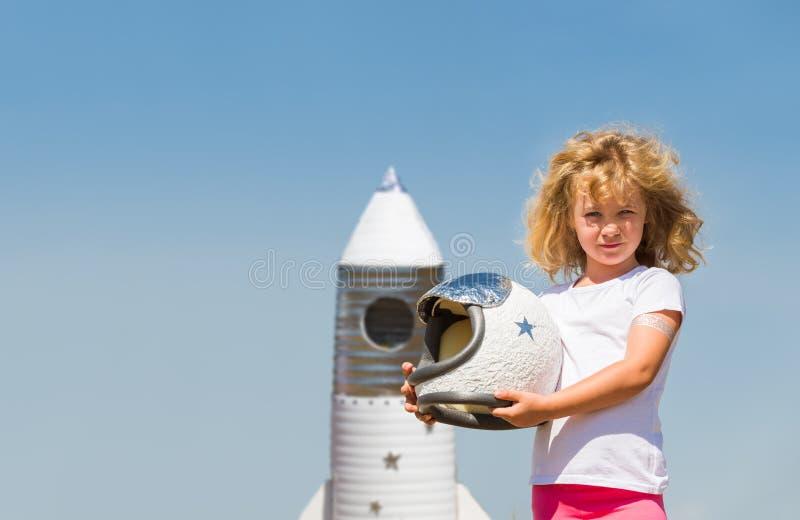 Stående av den blonda lilla flickan i en astronautdräkt med leksakraket som drömmer av att bli astronaut royaltyfria bilder