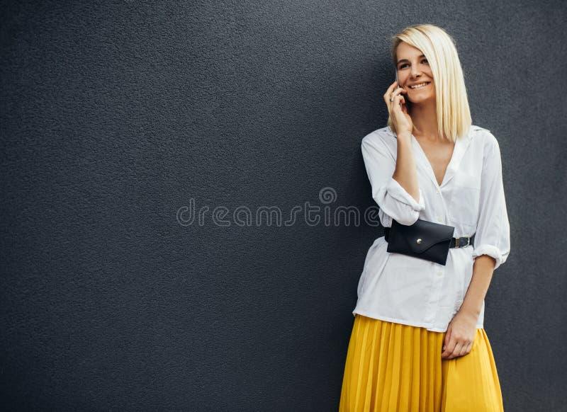 Stående av den blonda lyckliga affärskvinnan som ler och står mot grå byggnads vägg, medan tala på den smarta telefonen härligt royaltyfria foton