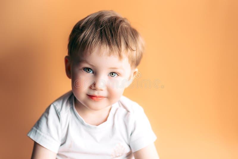 Stående av den blonda lyckliga glade härliga gulliga pysen som ser kameran på orange bakgrund arkivfoton
