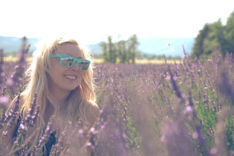 Stående av den blonda vuxna kvinnan i ett lavendelfält som ler, i den guld- timmen för solnedgång fotografering för bildbyråer