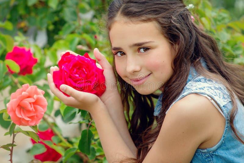 Stående av den brunögda lilla flickan med en ros arkivfoton