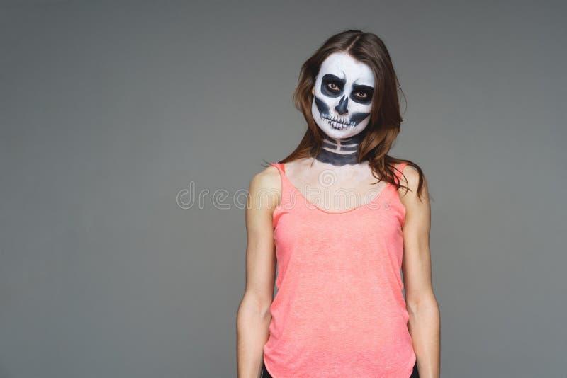 Stående av den brunhåriga kvinnan med att skrämma halloween skelett- makeup i rosa fotboll och en tatuering på hans arm över grå  fotografering för bildbyråer